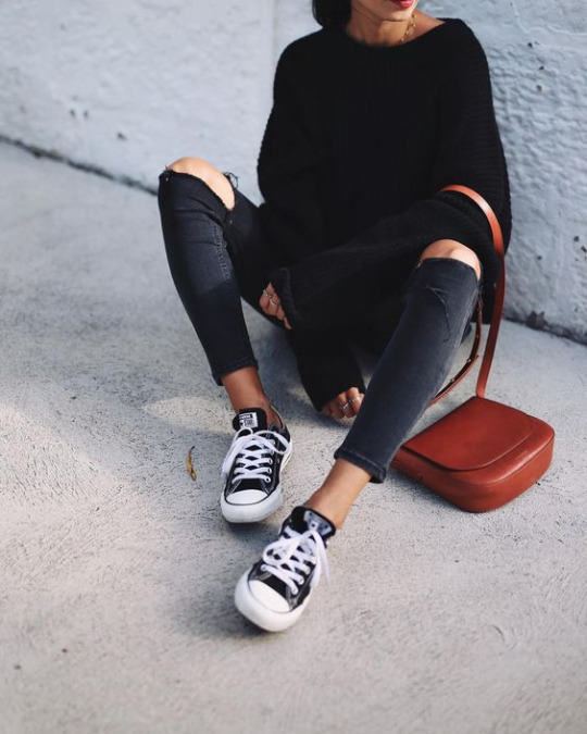 Andy Csinger wears black and white low-top converse with rolled distressed jeans, and a cosy black knitted sweater. Sweater: H&M, Jeans: Topshop, Shoes: Converse.