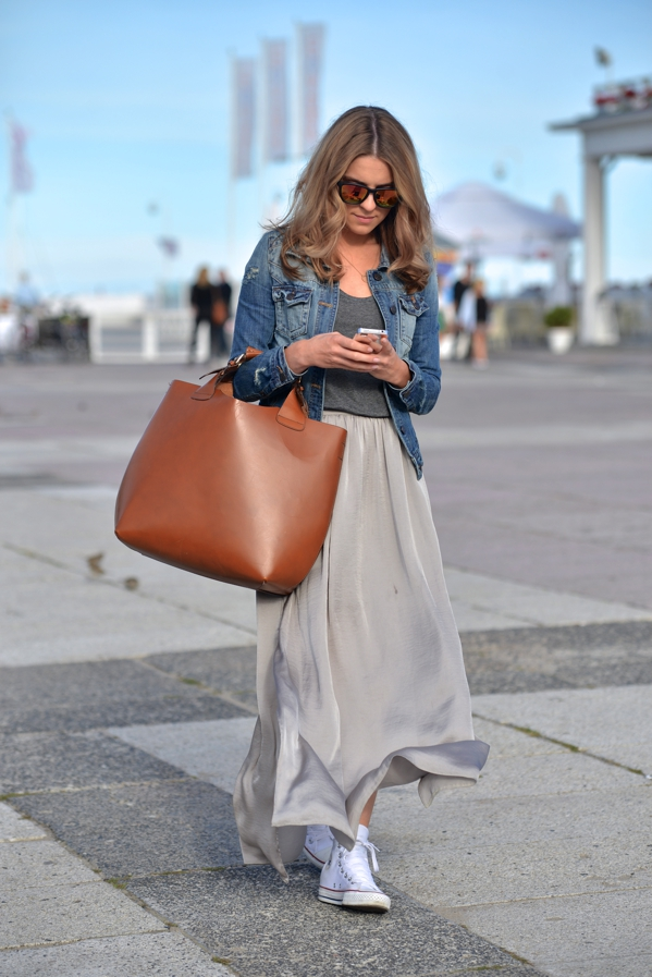 Converse will look awesome worn with a maxi skirt! Katarzyna Tusk shows how to wear white converse, pairing them with a flowing grey skirt adn a cropped denim jacket. We love this fresh spring style! Jacket: River Island, Shoes: Converse, Top: COS, Skirt: Taranko, Bag: Zara.