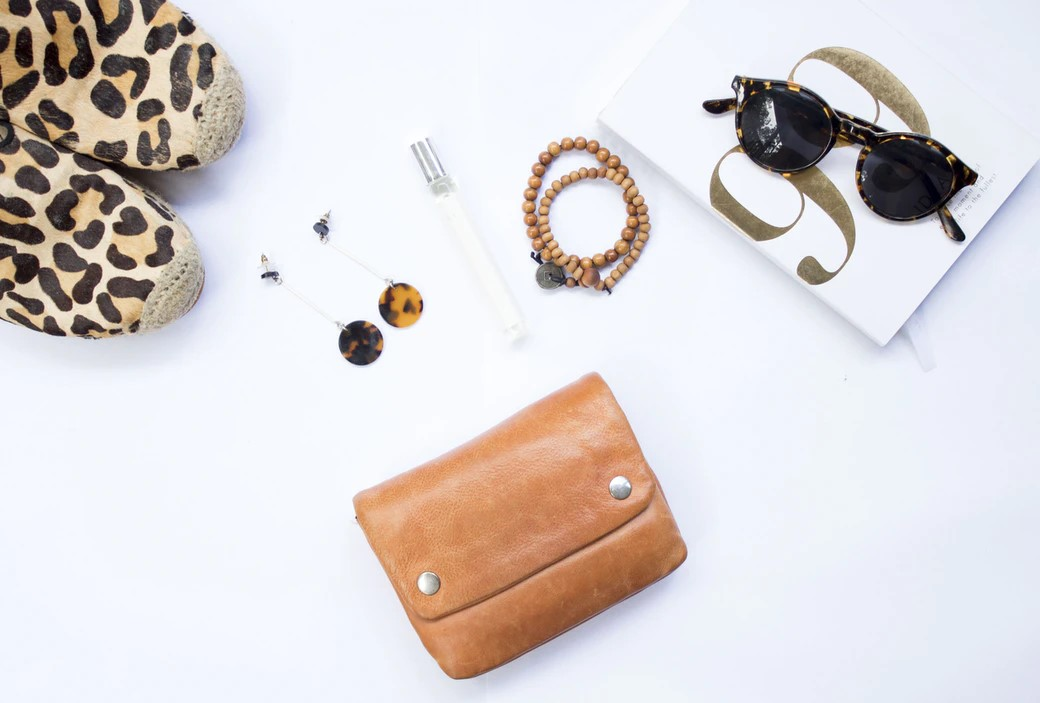 wallet sunglasses jewelry and other accessories on a white surface