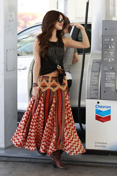 Selena Gomez Selena Gomez looks dolled up in a Native American inspired outfit as she pumps gas in Hollywood. The 20 year old 'Wizards of Waverly Place' star wore a long flowing summer skirt, cowboy boots and a belly baring tank top as she stopped by the gas station.