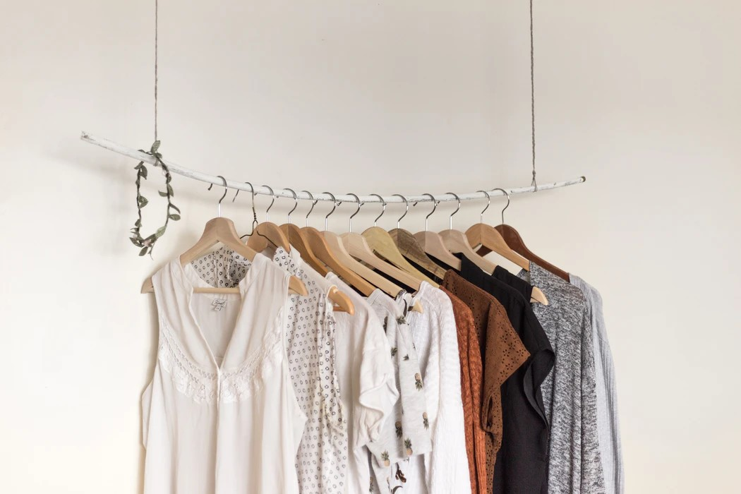 white brown and grey shirts hanging on a rack against a white wall