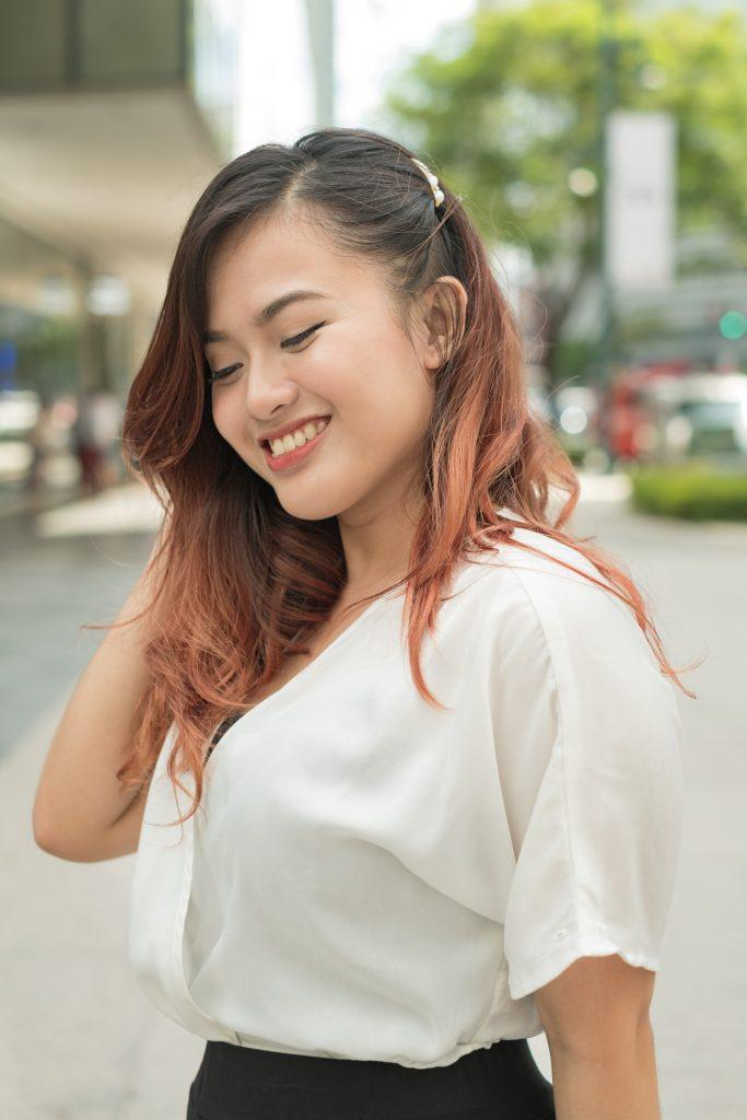 Asian woman with mahogany hair and hair clip hairstyle smiling