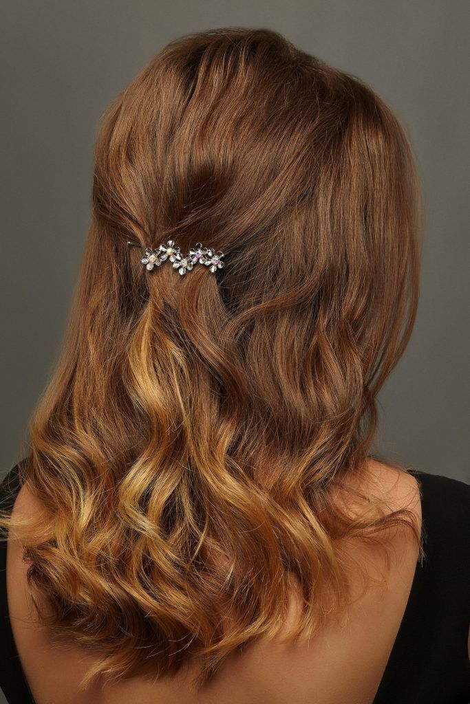 back view of model is shown to reveal her metallic clip on a half updo